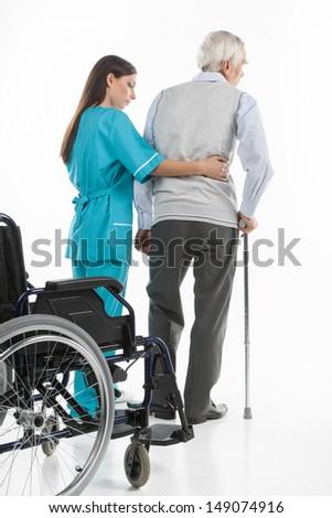 Senior care. Confident nurse helping senior men to walk while isolated on white - stock photo