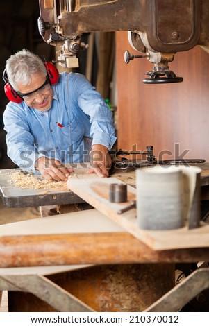 Senior carpenter using bandsaw to cut wood in workshop - stock photo