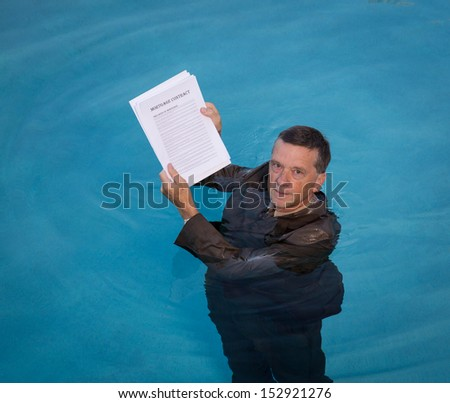 Senior caucasian businessman in suit up to neck in deep blue water worried about being underwater with mortgage payments - stock photo