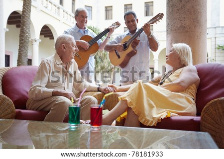 senior caucasian couple sitting in bar at hotel and listening to musicians playing guitar. Horizontal shape - stock photo