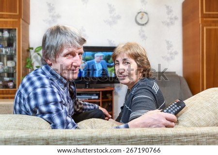 Senior Caucasian couple sitting in front of TV and turning back on couch - stock photo