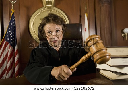 Senior Caucasian judge holding mallet in courtroom - stock photo
