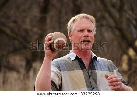 senior Caucasian male throwing football - stock photo