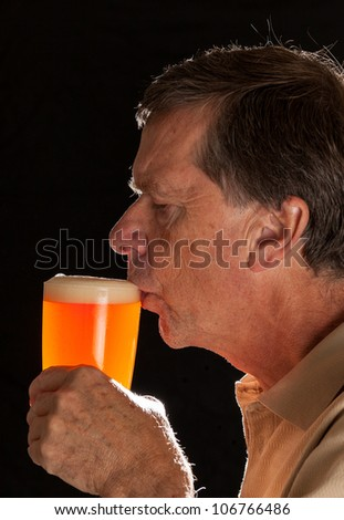 Senior caucasian man in profile drinking from a pint glass of beer or lager - stock photo