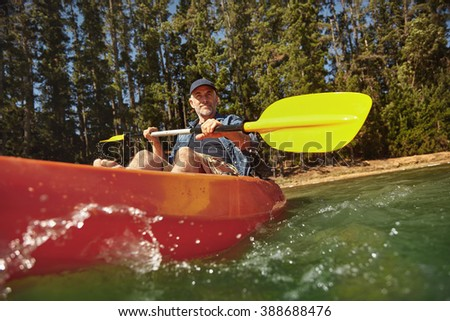 Senior caucasian man paddling a kayak in lake. Mature man canoeing on summer day.