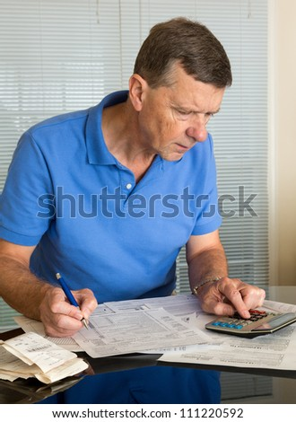 Senior caucasian man preparing tax form 1040 for tax year 2012  with receipts and calculator - stock photo