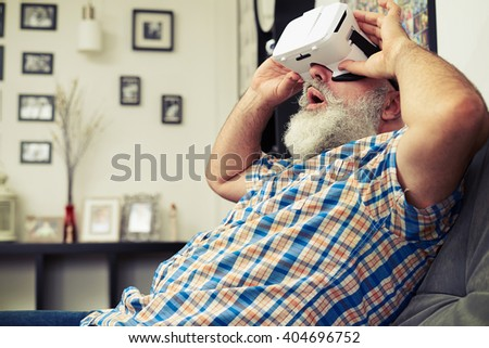 Senior Caucasian man shocked by what he sees using white virtual reality headset glasses