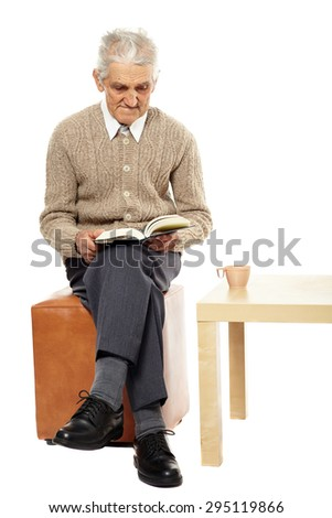 Senior caucasian man with white hair reading a book - stock photo