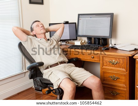 Senior caucasian man working from home in shorts with desk with two monitors - stock photo