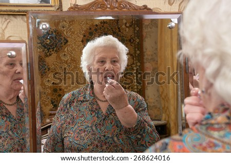 Senior caucasian woman about ninety years old puts on lipstick before a three sided mirror in her bed room - stock photo