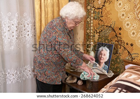 Senior caucasian woman about ninety years old wipes the dust from the bedside table in her bed room. Her framed portrait stands on bedside table. - stock photo