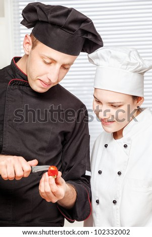 Senior chef teaches young chef to decorate strawberry - stock photo