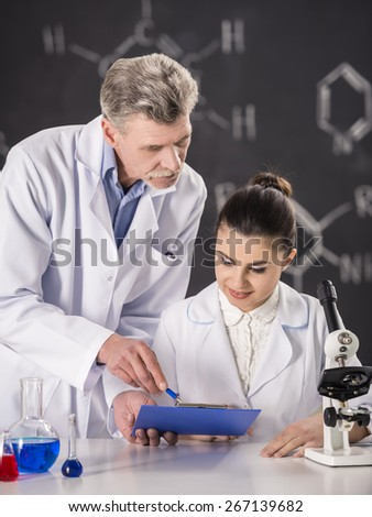 Senior chemistry professor and his assistant working  in  laboratory. - stock photo