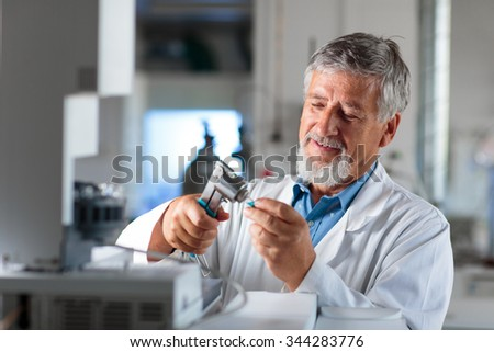 Senior chemistry professor/doctor in a lab (color toned image) - stock photo