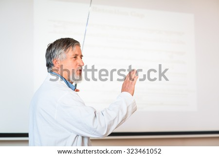Senior chemistry professor giving a lecture in front of classroom full of students (shallow DOF; color toned image) - stock photo