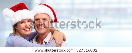 Senior Christmas santa couple over blue background - stock photo