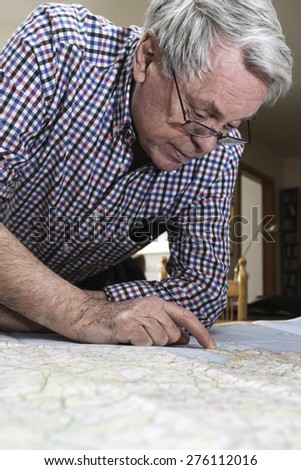 Senior citiizen reading map prior to going on vacation in Europe - stock photo