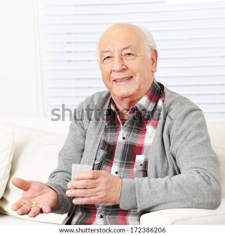 Senior citizen at home taking medical pill with cup of water - stock photo
