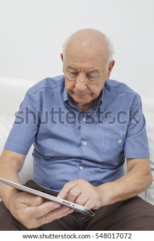 Senior citizen browsing the internet on his computer tablet