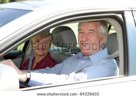 Senior citizen couple sitting in their car - stock photo