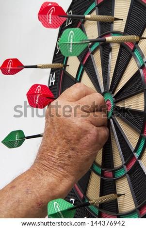 Senior citizen male  playing darts - pulling dart out of bull's eye - stock photo