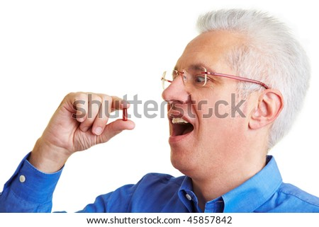 Senior citizen taking a red pill