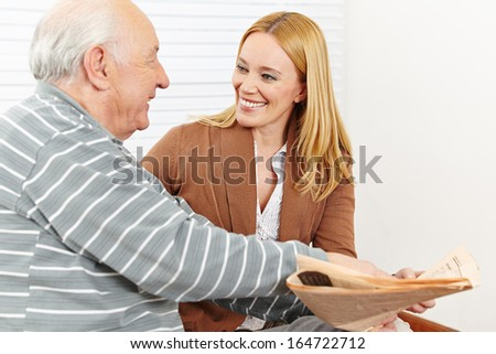 Senior citizen with smiling caregiver woman reading a newspaper - stock photo