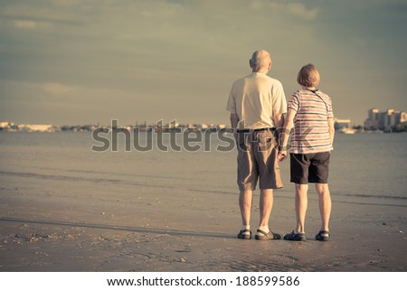 Senior citizens watching the sunset on a beach in Fort Myers, Florida. View from the back with copy space. - stock photo