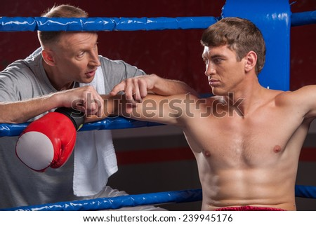 Senior coach advising boxer after end of round. two man in boxing ring talking - stock photo