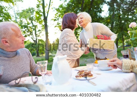 Senior congratulating woman with gift at her birthday party in a garden - stock photo