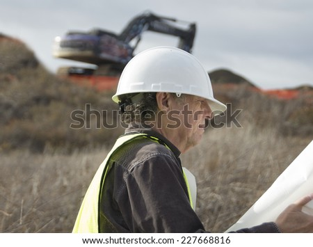 Senior construction man on a job site/Serious Construction Worker/Senior man with hard hat  - stock photo