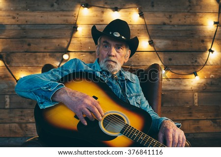 Senior country and western guitarist with beard sitting in chair. - stock photo