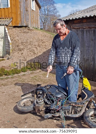 Senior country man outdoor, repairing old scooter
