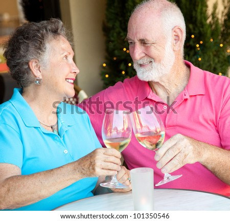 Senior couple at a cafe, enjoying a glass of white wine together. - stock photo