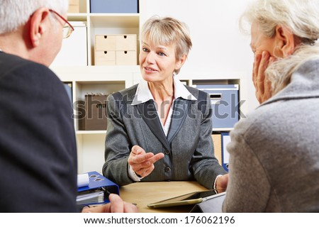 Senior couple at consultation with tablet computer in an office - stock photo