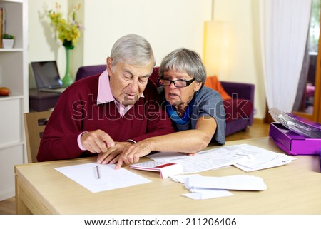 Senior couple at home calculating bills - stock photo