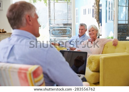 Senior Couple At Home Meeting With Financial Advisor - stock photo