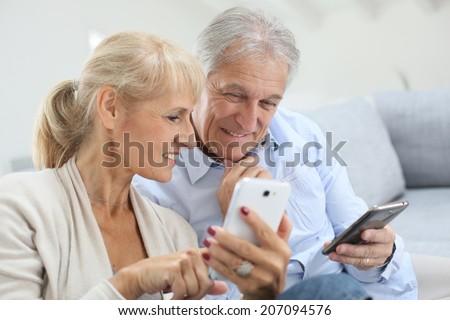 Senior couple at home using smartphone - stock photo