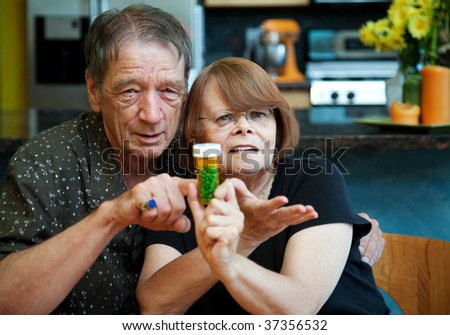 Senior couple at home with prescription bottle - stock photo