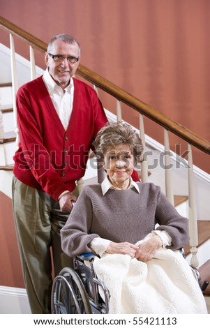 Senior couple at home, woman in 70s in wheelchair - stock photo
