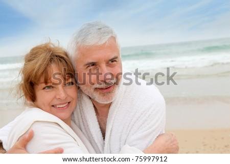 Senior couple at the beach with spa bathrobe - stock photo