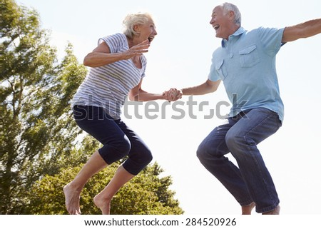 Senior Couple Bouncing On Trampoline In Garden - stock photo