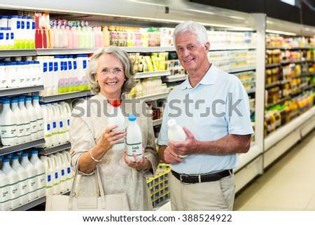 Senior couple buying milk at the supermarket - stock photo
