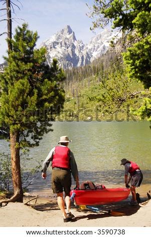 Senior couple carrying kayak to a lake - stock photo