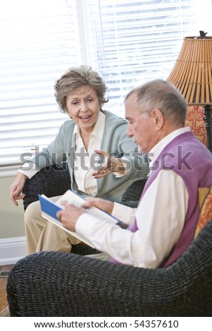 Senior couple chatting in living room reading book, focus on woman talking - stock photo