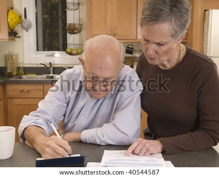Senior couple concerned about paying bills - stock photo
