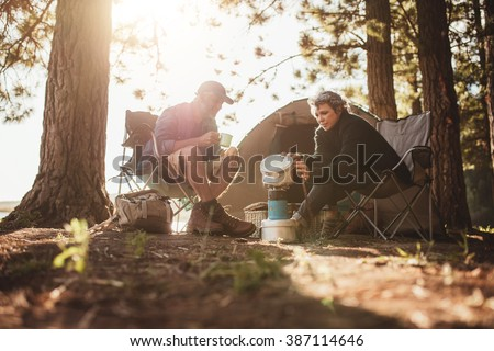 Senior couple cooking and making food outdoors on a camping trip. Mature man and woman sitting outside the tent on a summer day at campsite. - stock photo