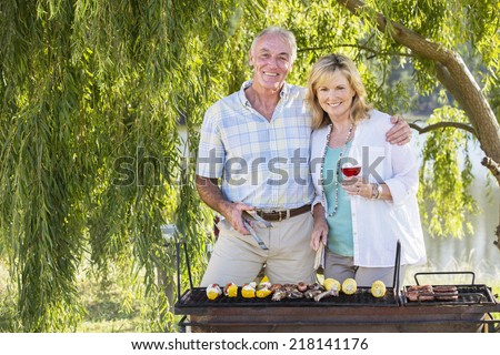 Senior Couple Cooking Barbeque In Countryside - stock photo