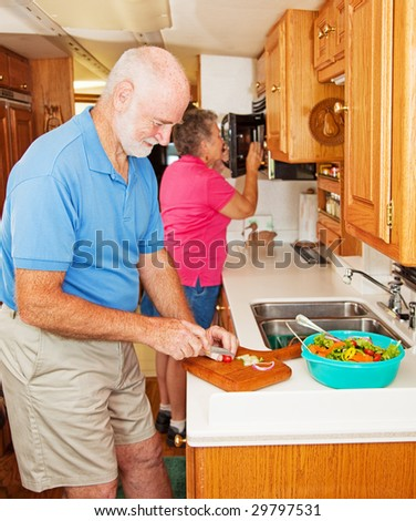 Senior couple cooking healthy dinner in the kitchen of their RV. - stock photo