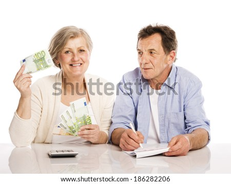 Senior couple counting money at the table, isolated on white background - stock photo